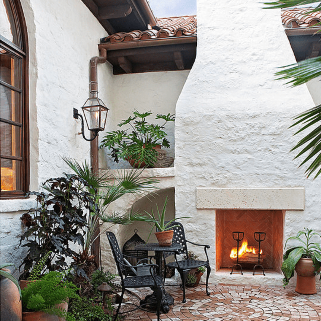 A white stucco outdoor fireplace with a tall chimney that seems built-in to the home behind it