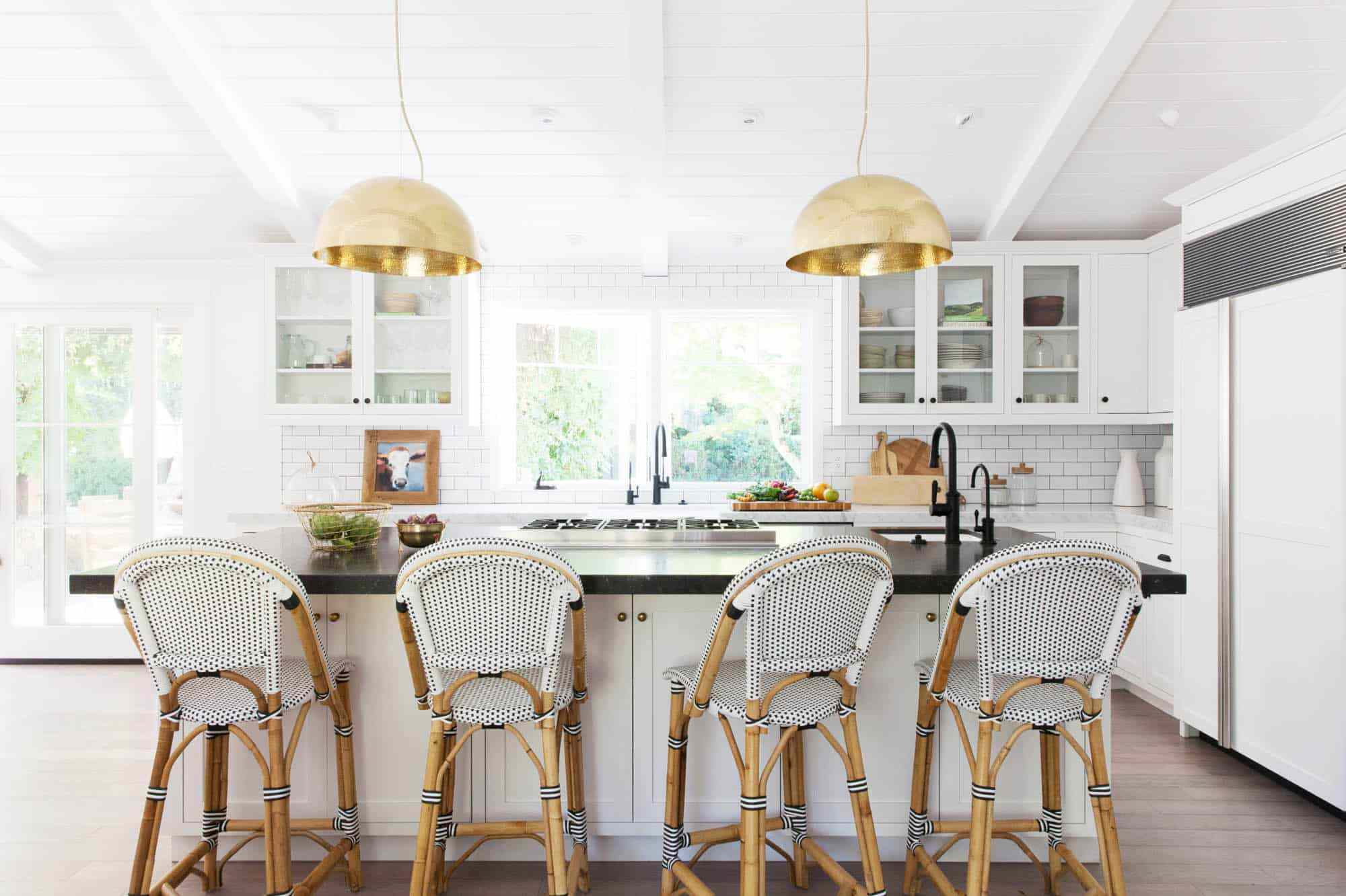 A white kitchen with bold barstools and large pendant lights