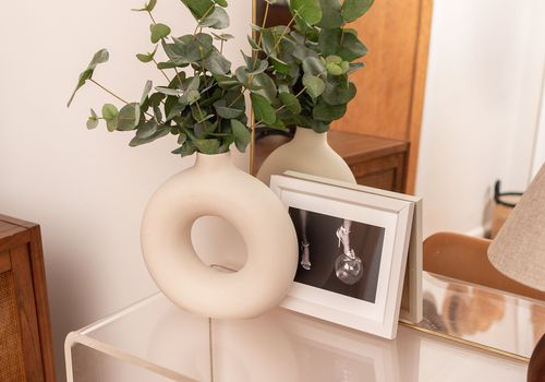 Donut vase filled with greenery.
