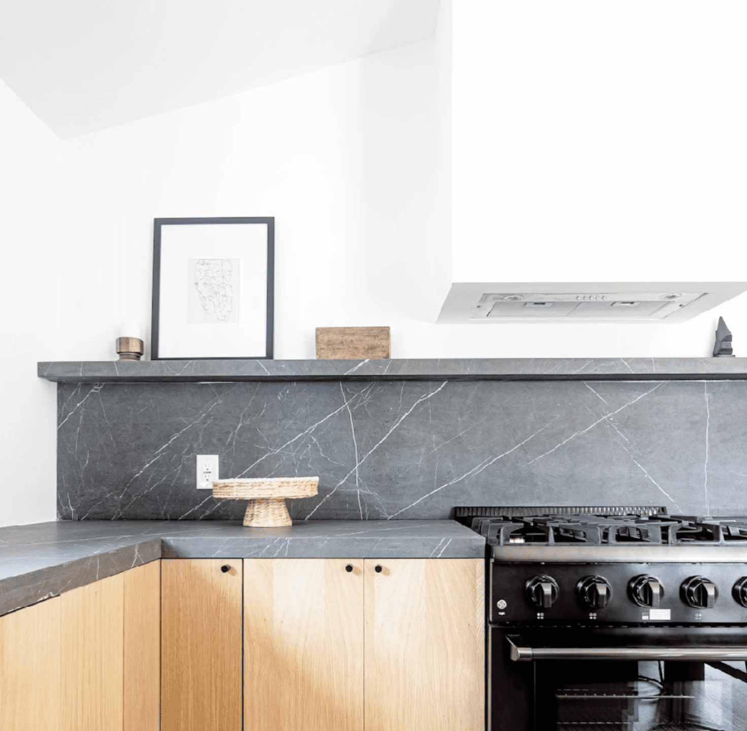 A minimalist kitchen with light wood cabinets and a gray marble backsplash