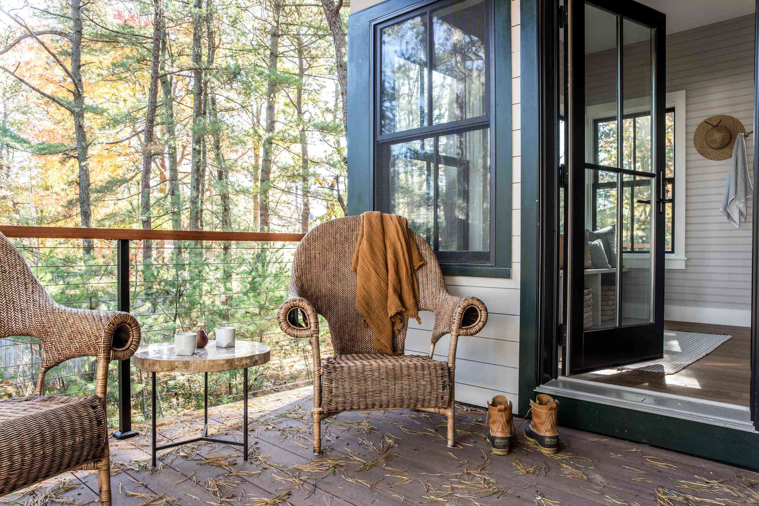 An outdoor deck with a breakfast nook craft from a small table and two woven chairs