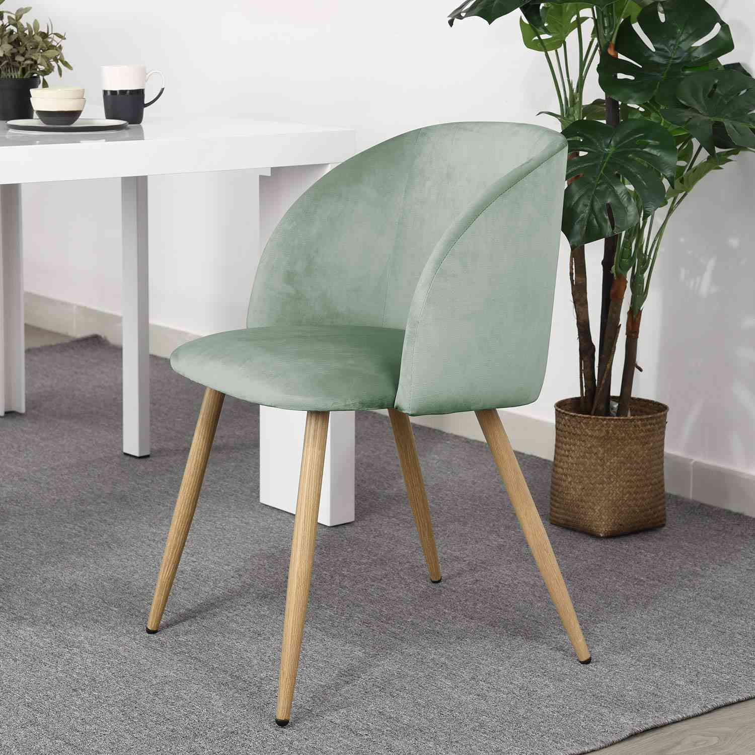 A green velvet dining chair with wooden legs on a gray rug.