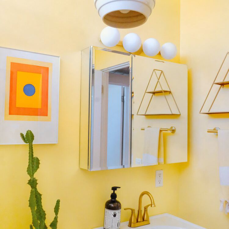 A powder room with vibrant yellow walls and bold fixtures