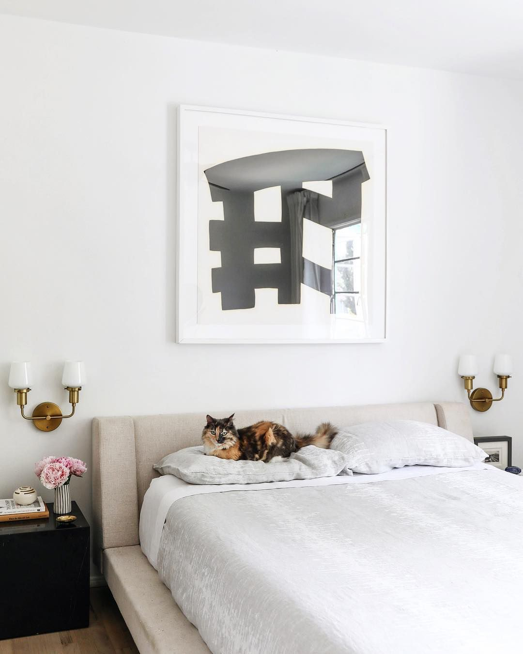 Bedroom with black and white painting above bed
