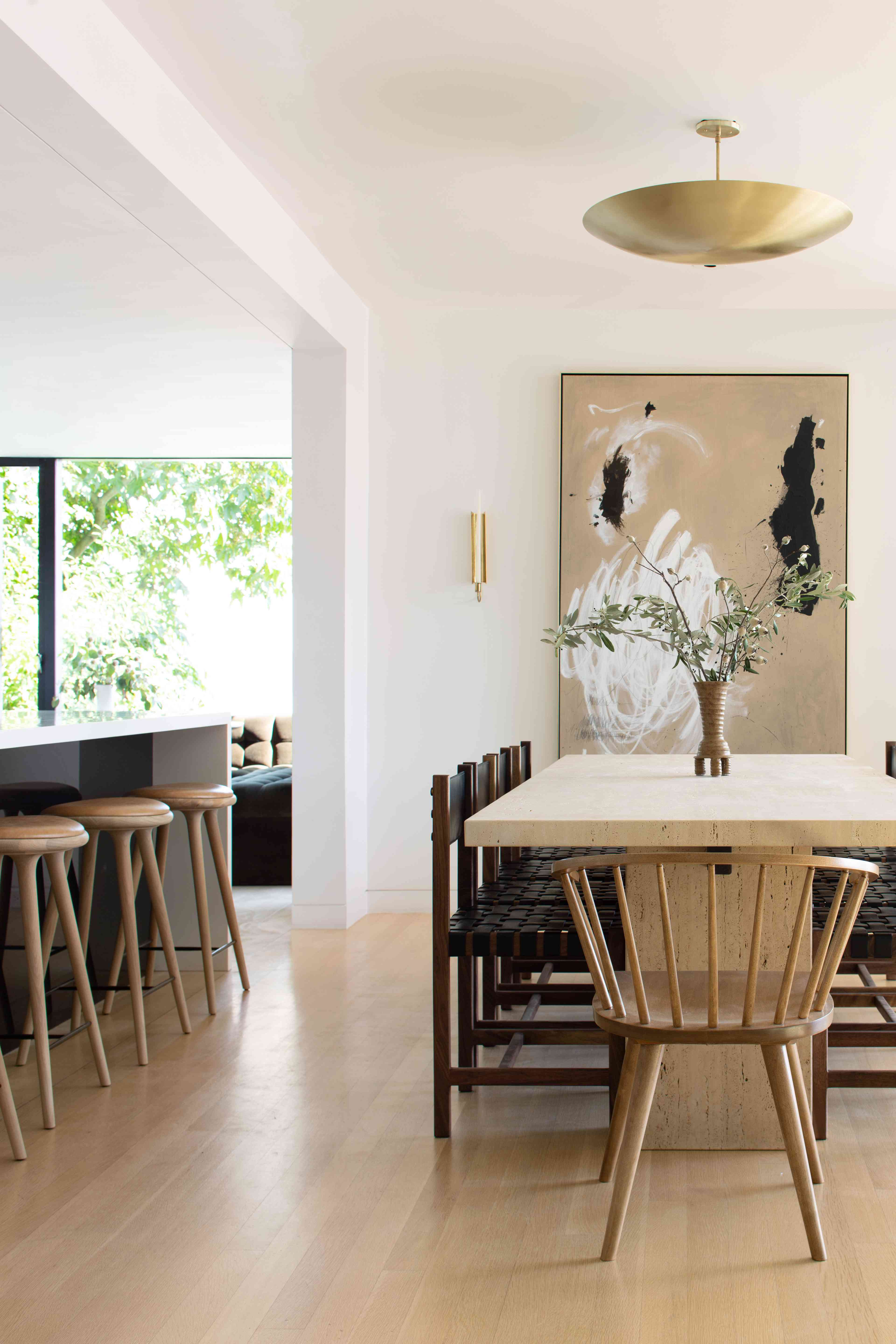Bright modern dining area with gold pendant light.