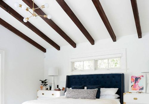 Exposed beam ceilings in bedroom with textured carpet