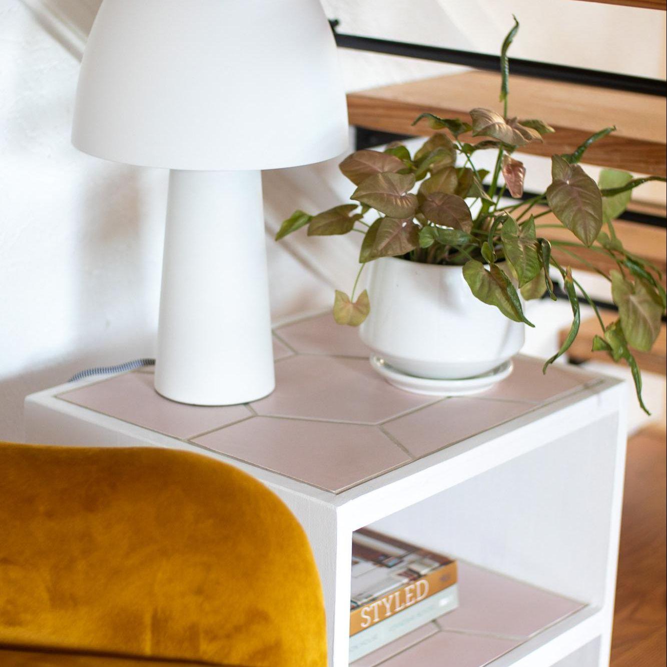 Retro tiled nightstand with mushroom lamp.