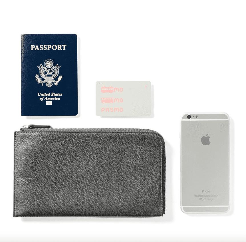 A gray travel wallet alongside an iPhone, passport and transport ticket.