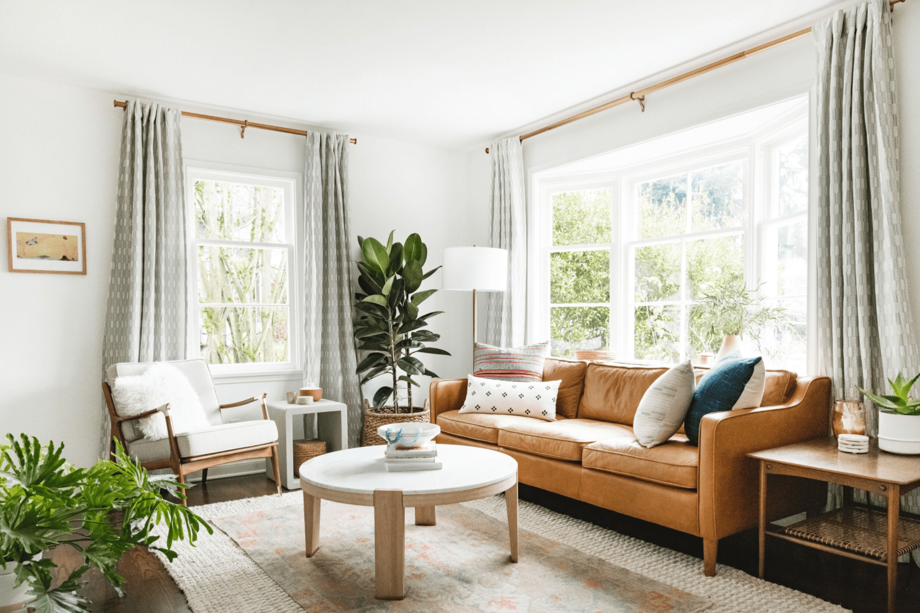Living room features layered area rugs, leather couch, potted plants