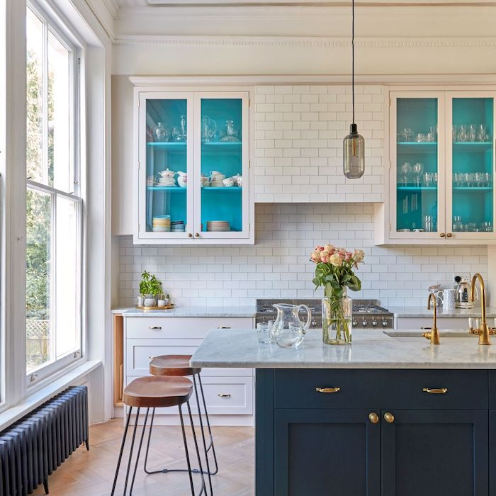 kitchen with white subway tile backsplash, white cabinets with glass panelling, island featuring dark blue cabinets and marble counter