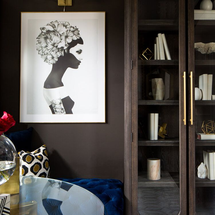 Foreroom features chocolate brown walls, blue velvet bench, round glass table