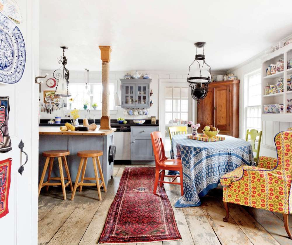 Country kitchen with lots of patterned textiles and blue built-ins