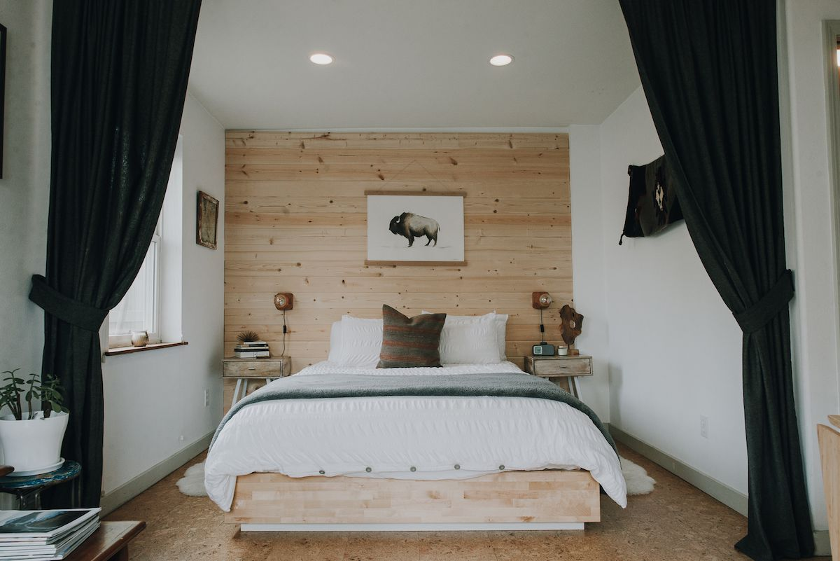 A bedroom with a wood-lined wall