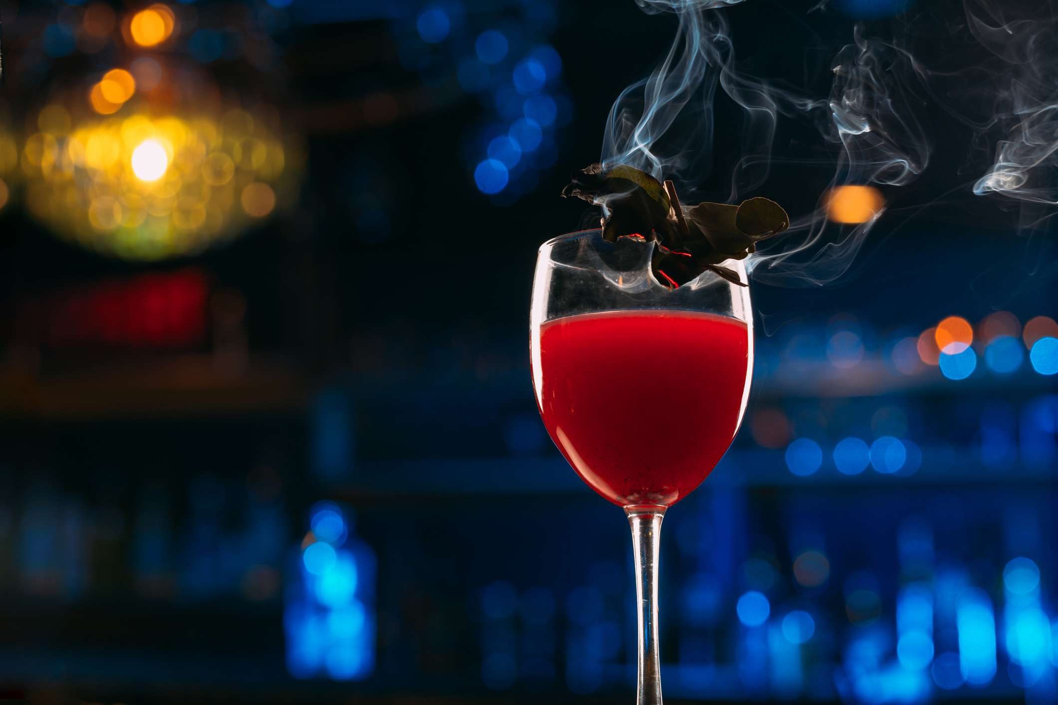 Un cóctel de color rojo en una copa de vino con una guarnición humeante.
