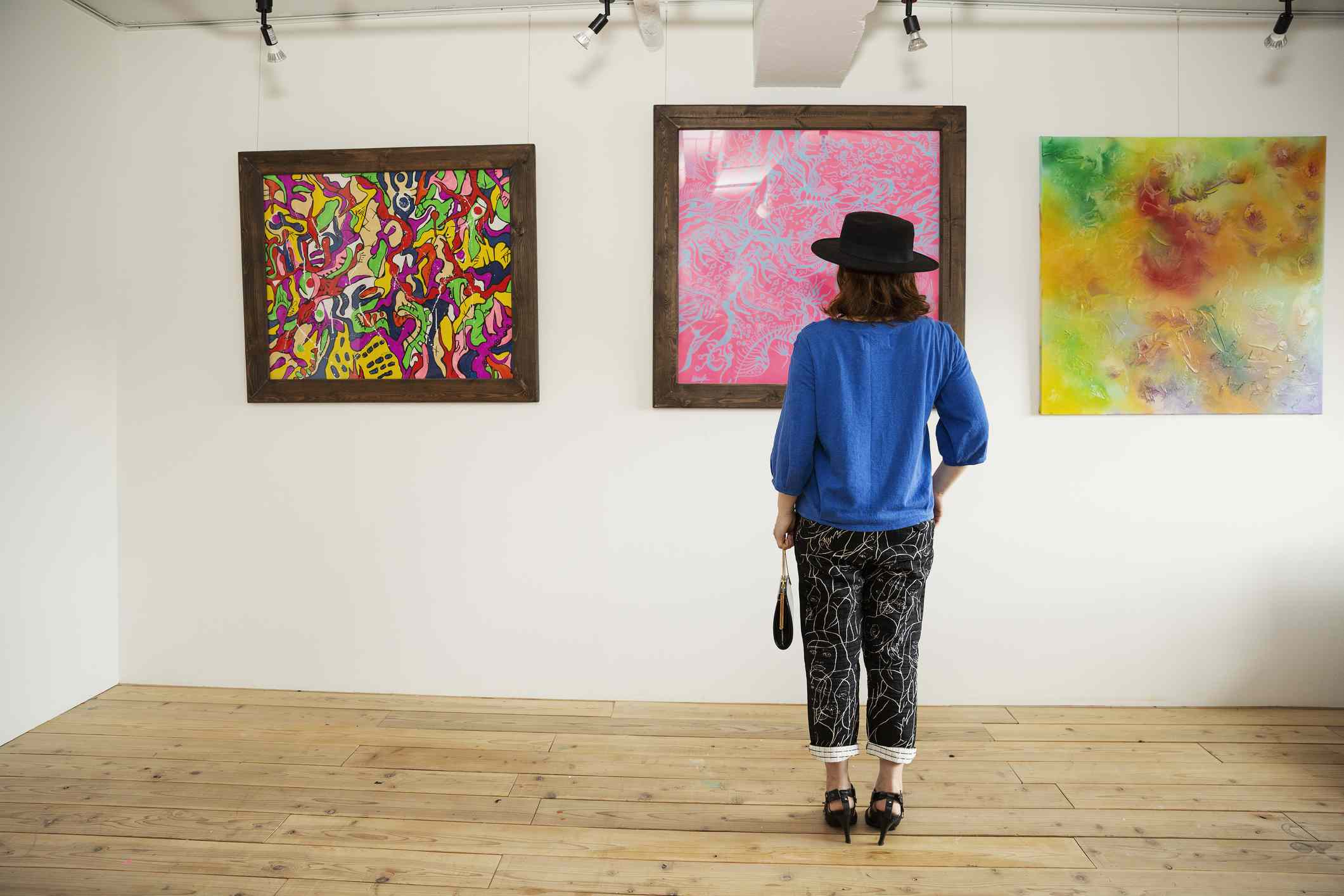 Woman stands in front of abstract paintings in art gallery