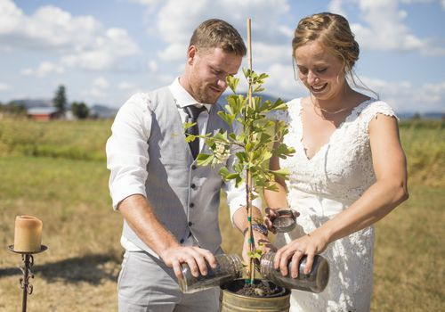 A bride and groom engaging in a tree planting ceremony.