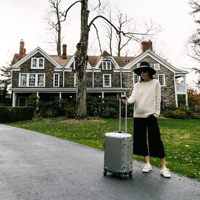 a woman with a rolling back waiting for a ride to the airport in front of a house