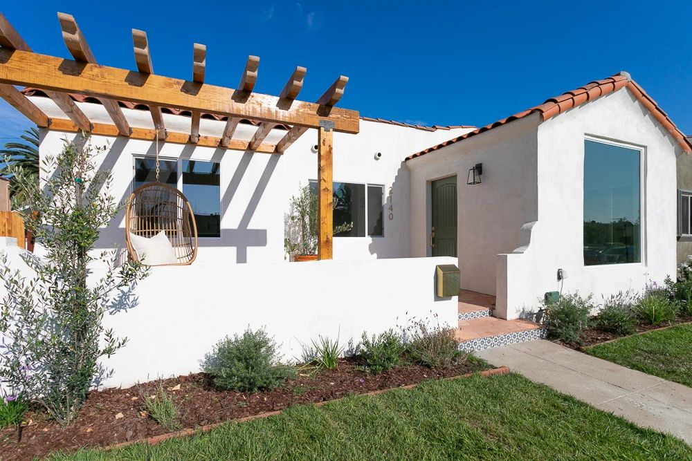 White exterior house with pergola and hanging chair.