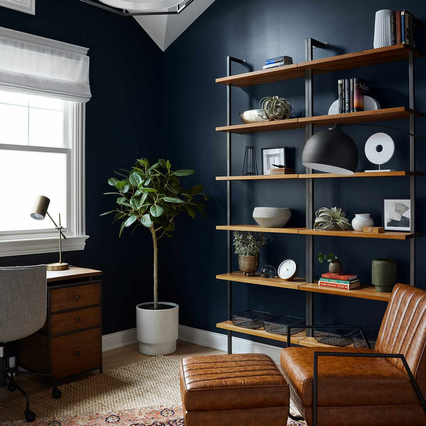 A home office with a wooden desk against a wall and a leather lounge chair in a corner