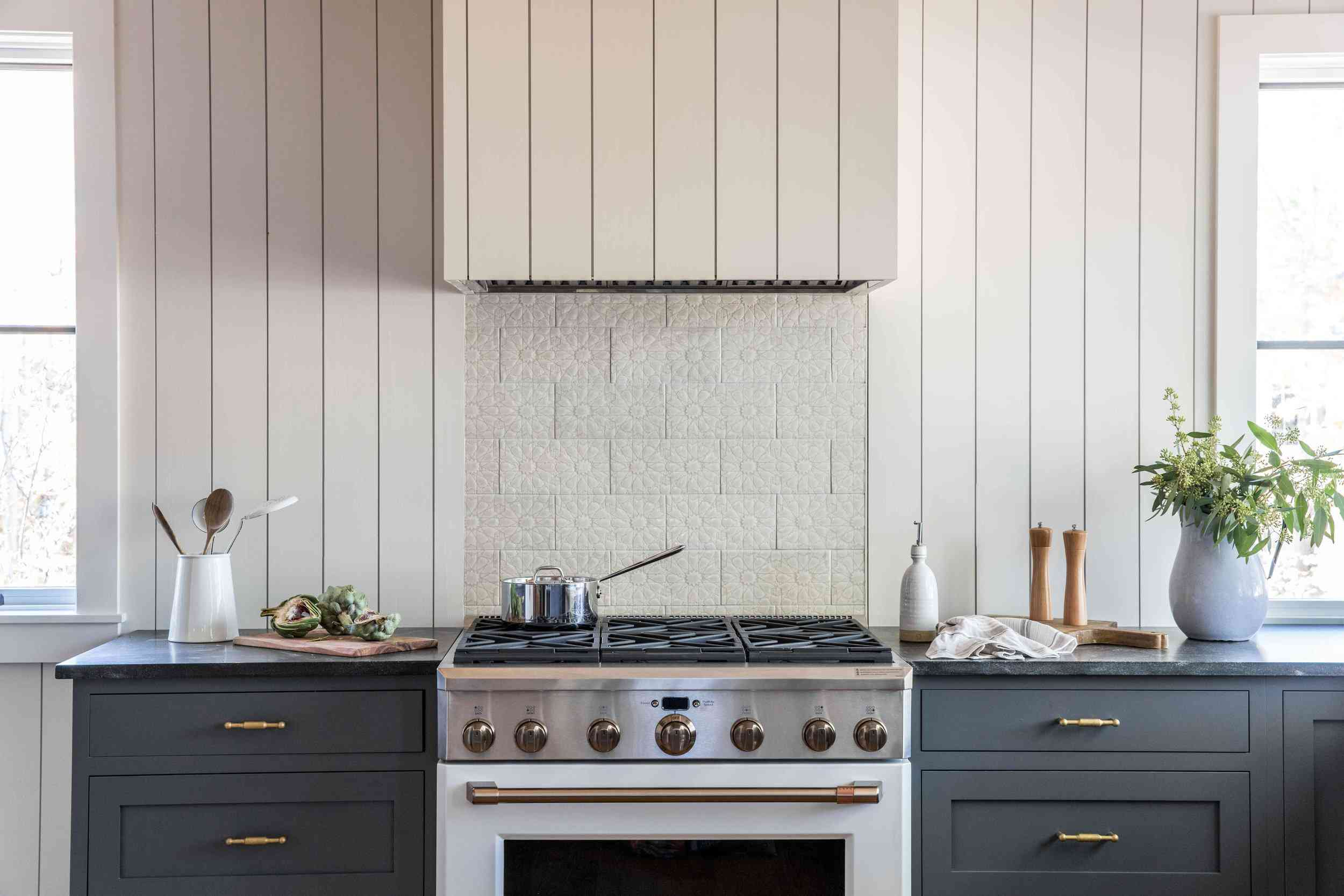 A backsplash lined with white tiles that have been textured to suggest a floral print