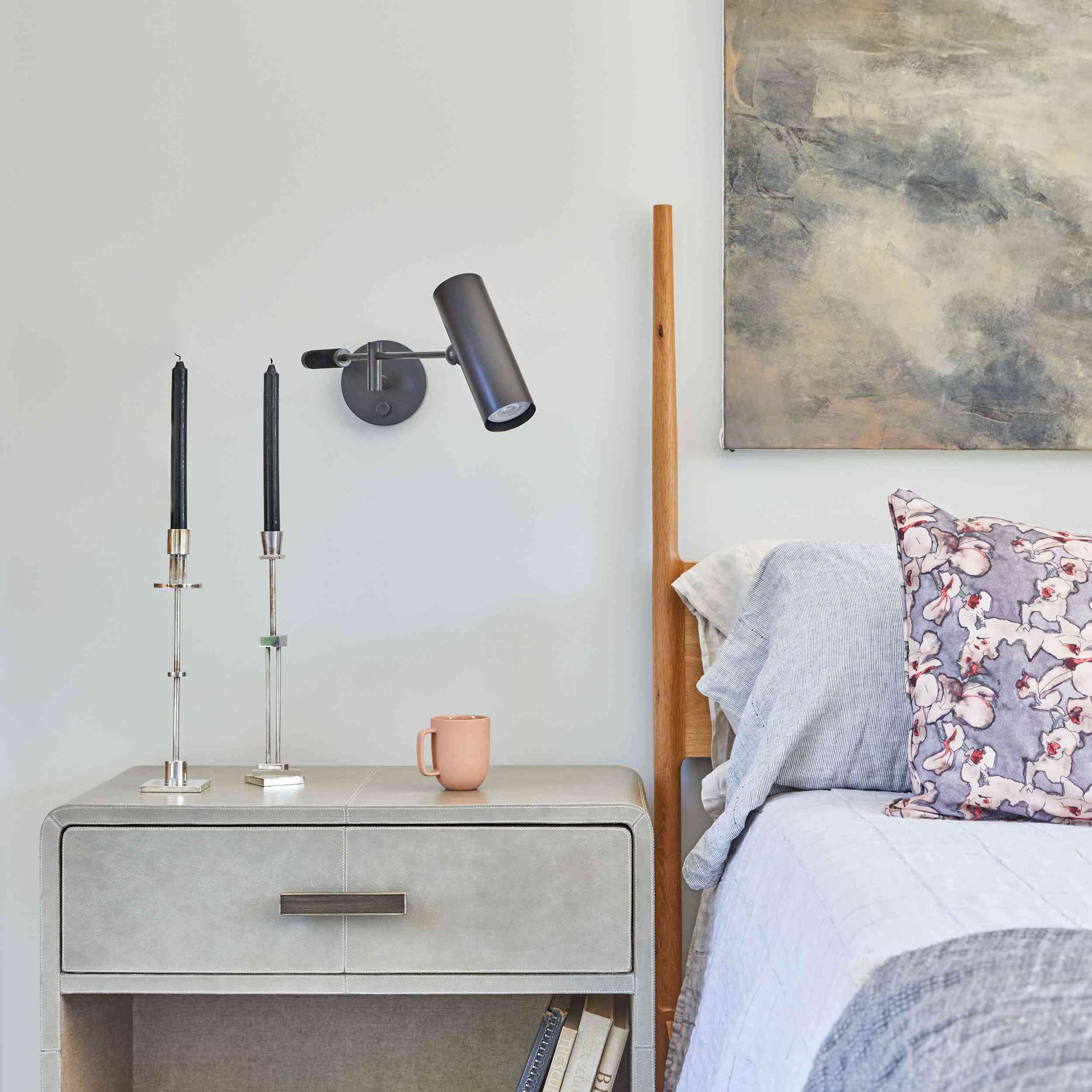 A bedroom with a sleek, industrial sconce