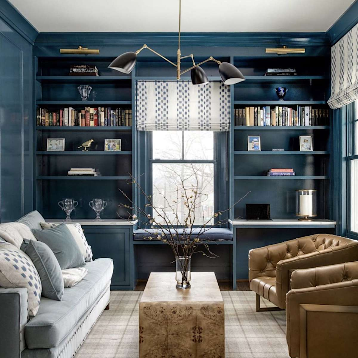 ocean blue symmetrical bookcases with brown leather seating