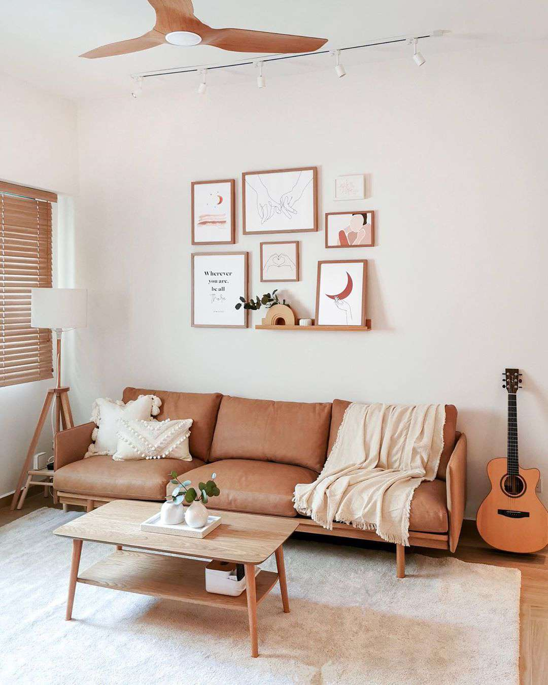 Soft pink living space with overhead lighting and corner lamp.