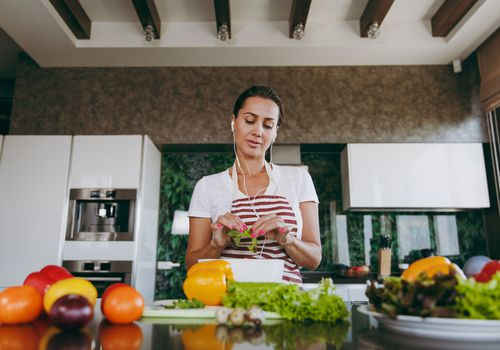 Young woman with headphones in the ears holding vegetables in hands in kitchen with laptop on the table. Vegetable salad. Dieting concept. Healthy lifestyle. Cooking at home. Prepare food