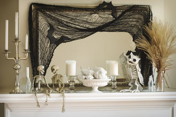 Spooky mantle decor for Halloween with skeletons and cobwebs