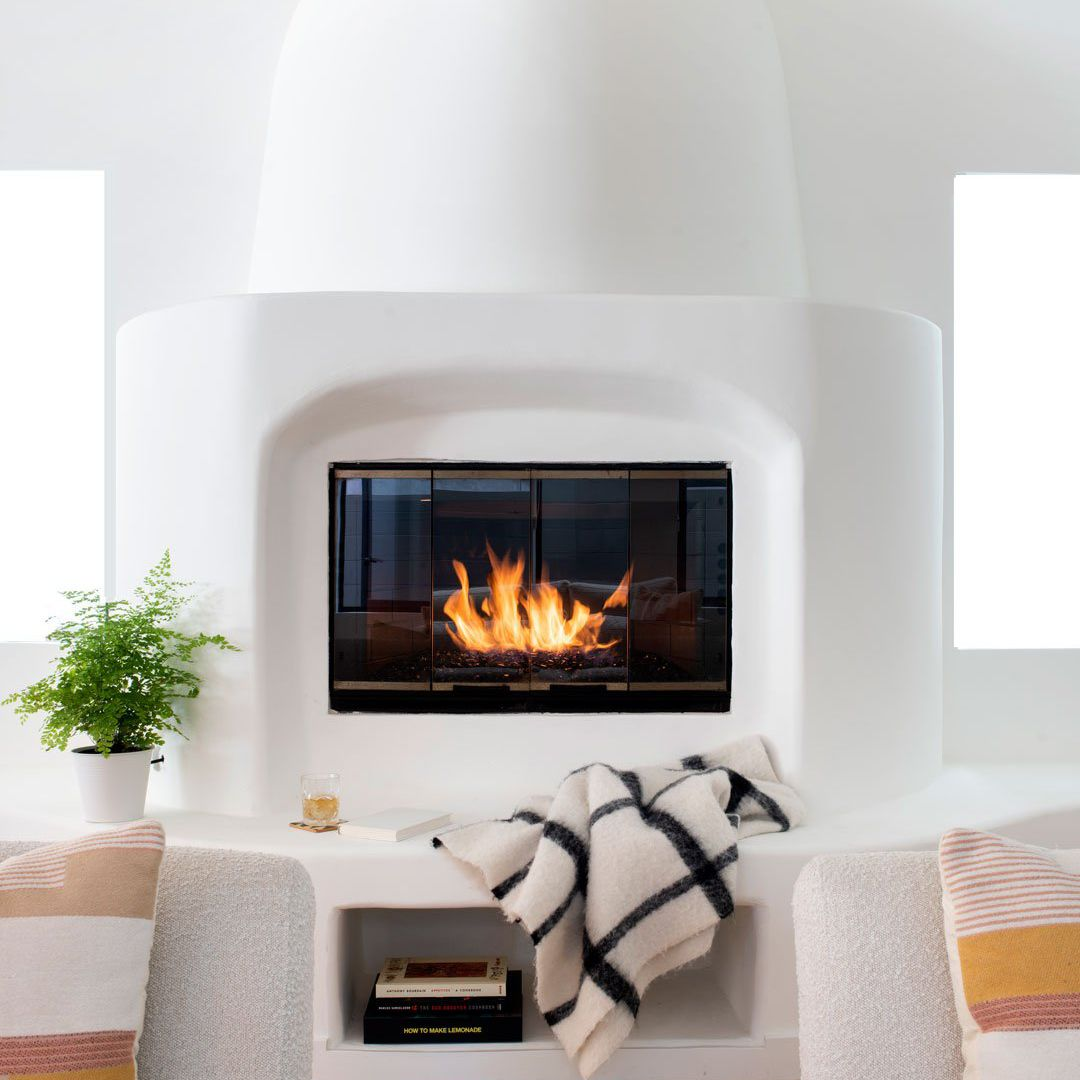 White painted clay fireplace and hearth with cozy accessories