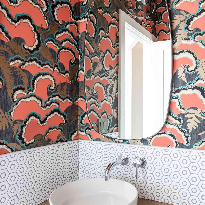 A bathroom with coral and aqua printed wallpaper