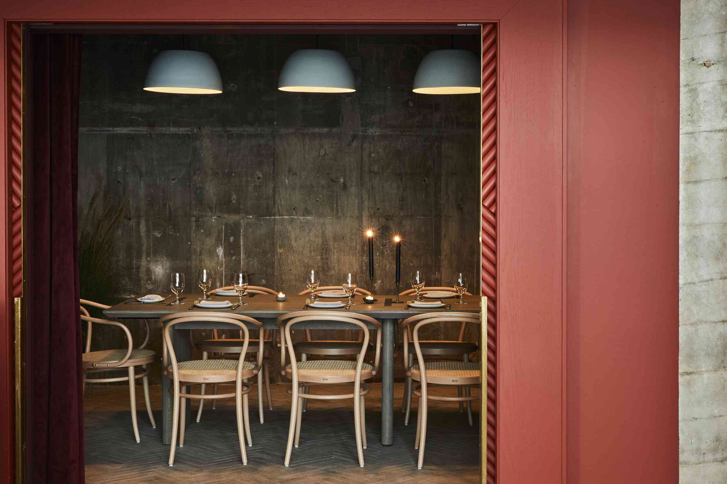 A red wall leading into a low-lit dining room