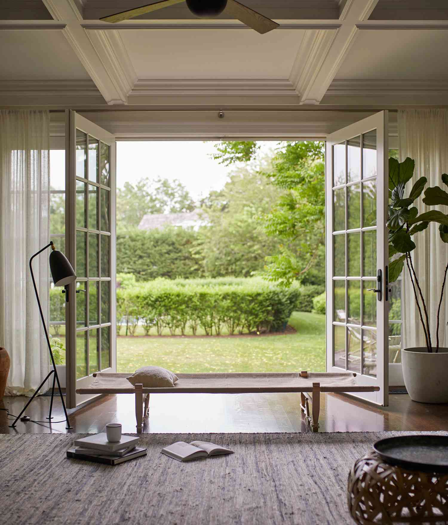 Living room with open French doors looks out on green lawn
