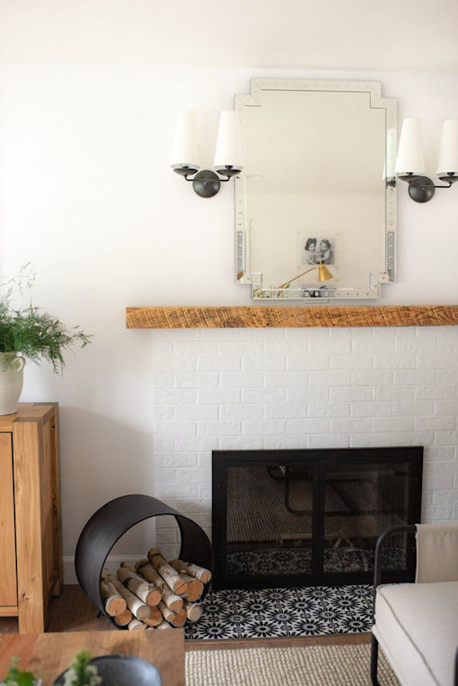 White fireplace with logs.
