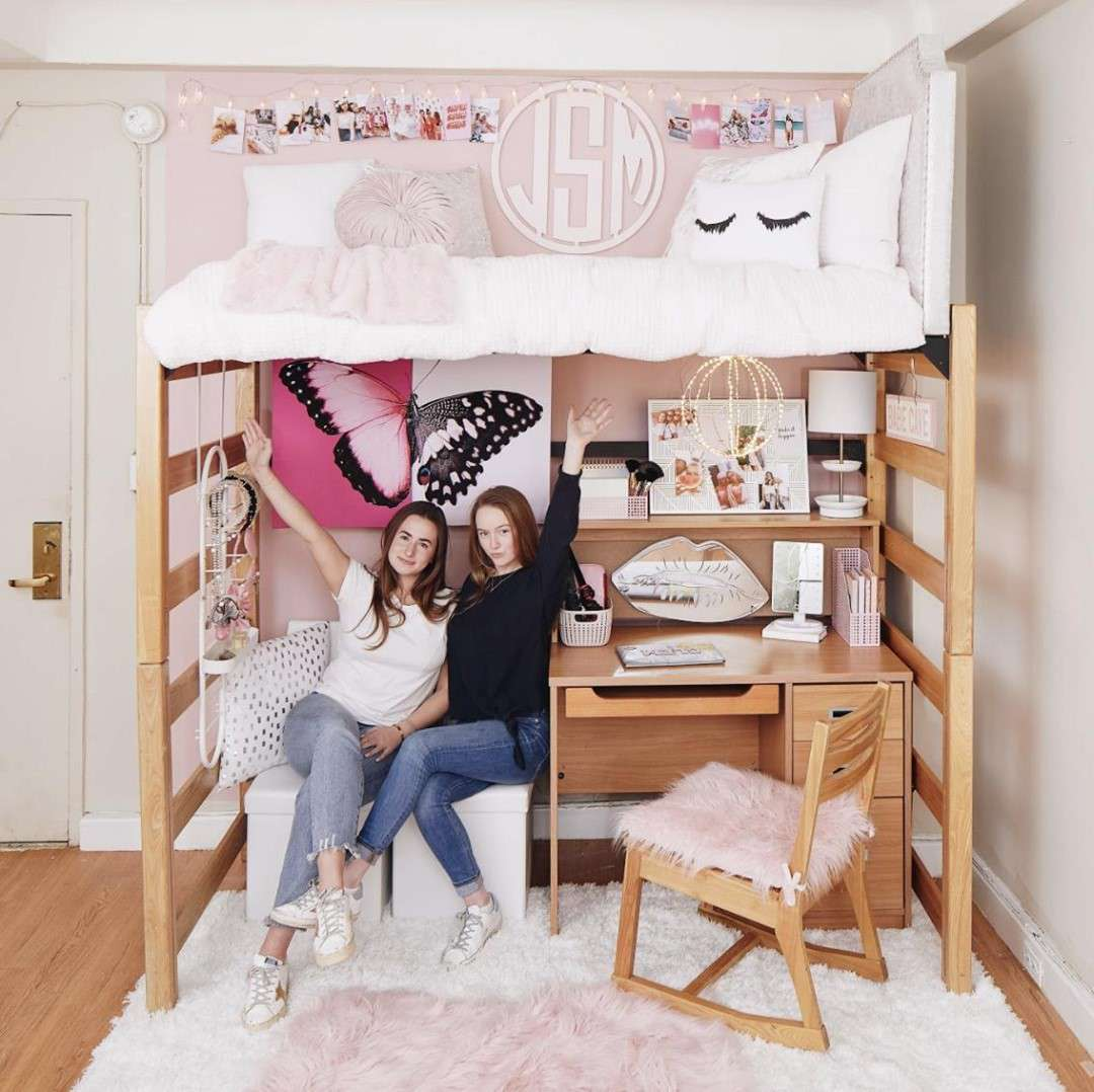 Two girls underneath their lofted dorm bed.