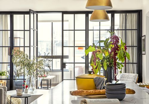 Sunny apartment kitchen with black framed windows,