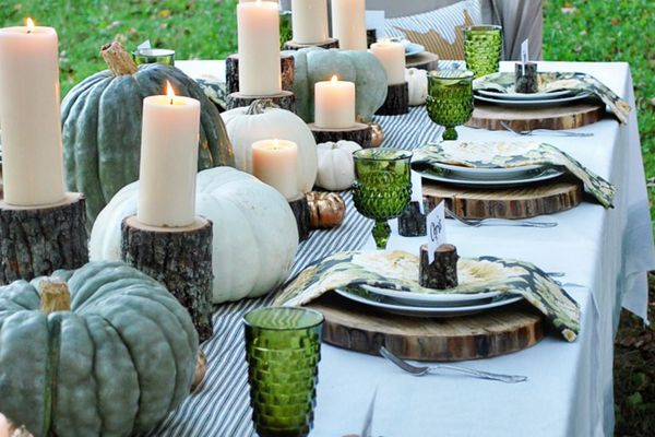 A large dining table set outdoors, featuring a tablescape of gourds, pillar candles, wooden chargers, and green glassware.
