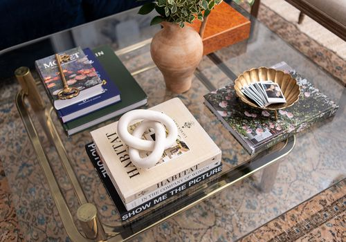 Glass coffee table with books and other trinkets.