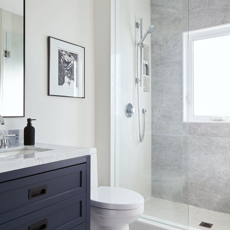 Gray and white bathroom with marble sink, zig zag pattern til floor, step-in shower
