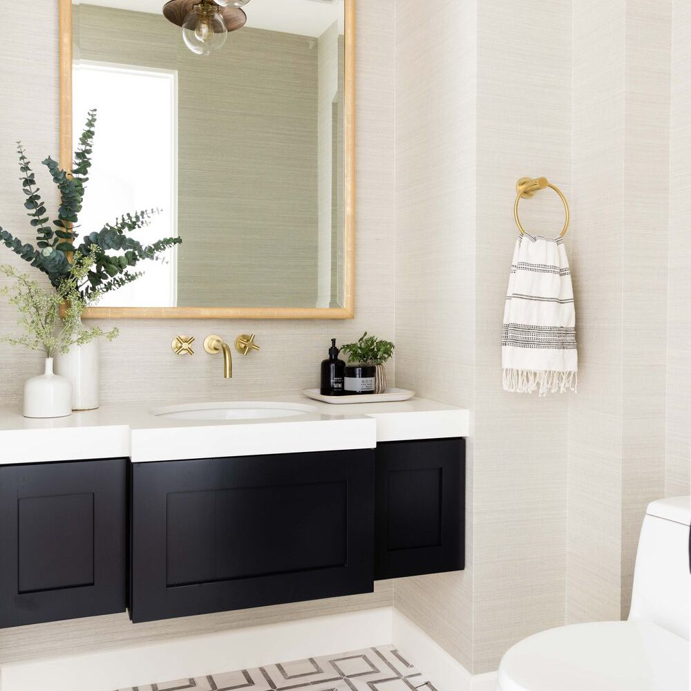 A bathroom lined with ivory wallpaper