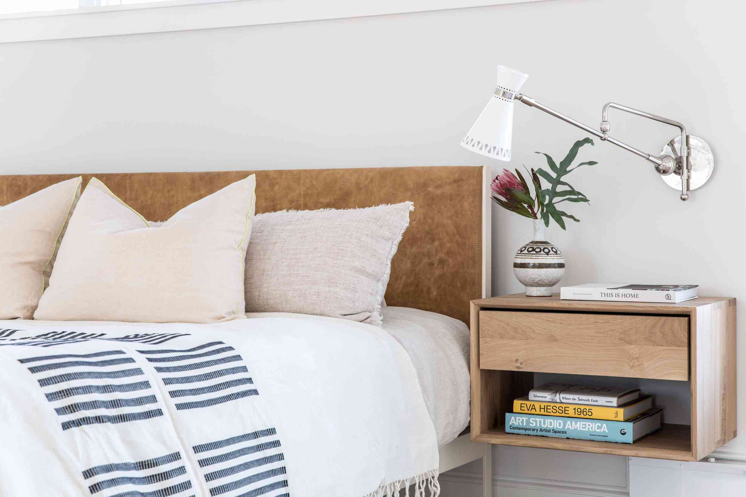 A bedroom with a floating nightstand that's been built-in to the wall