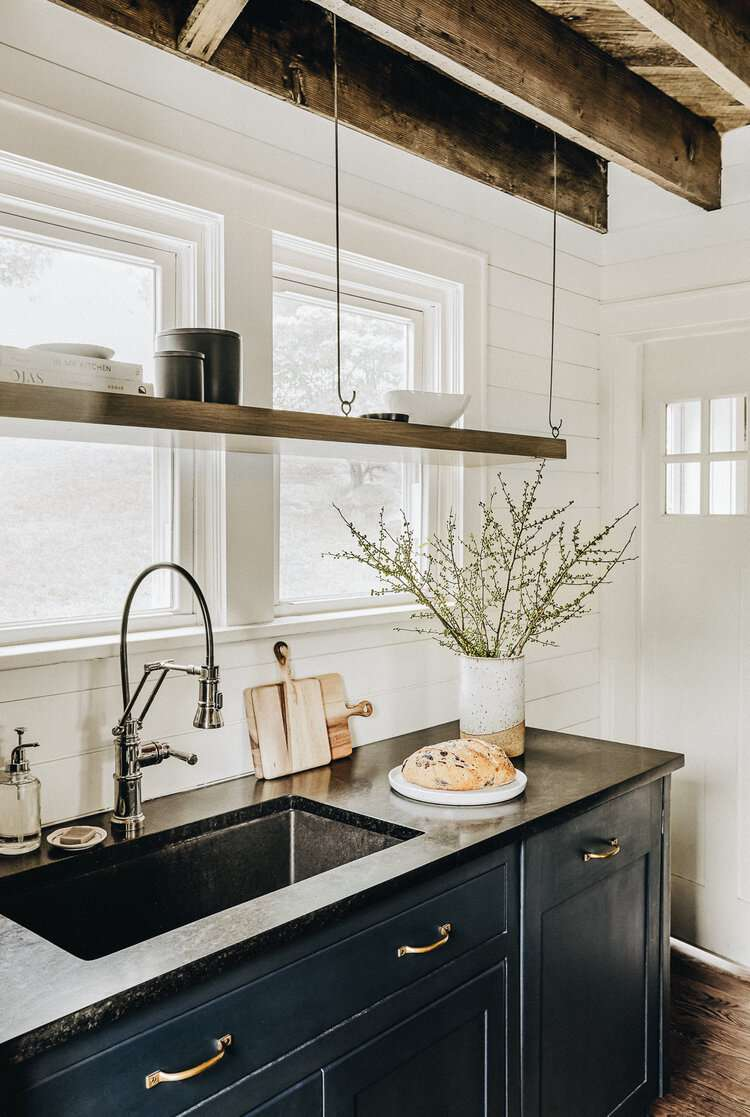 A kitchen with a backsplash made of painted white wood paneling