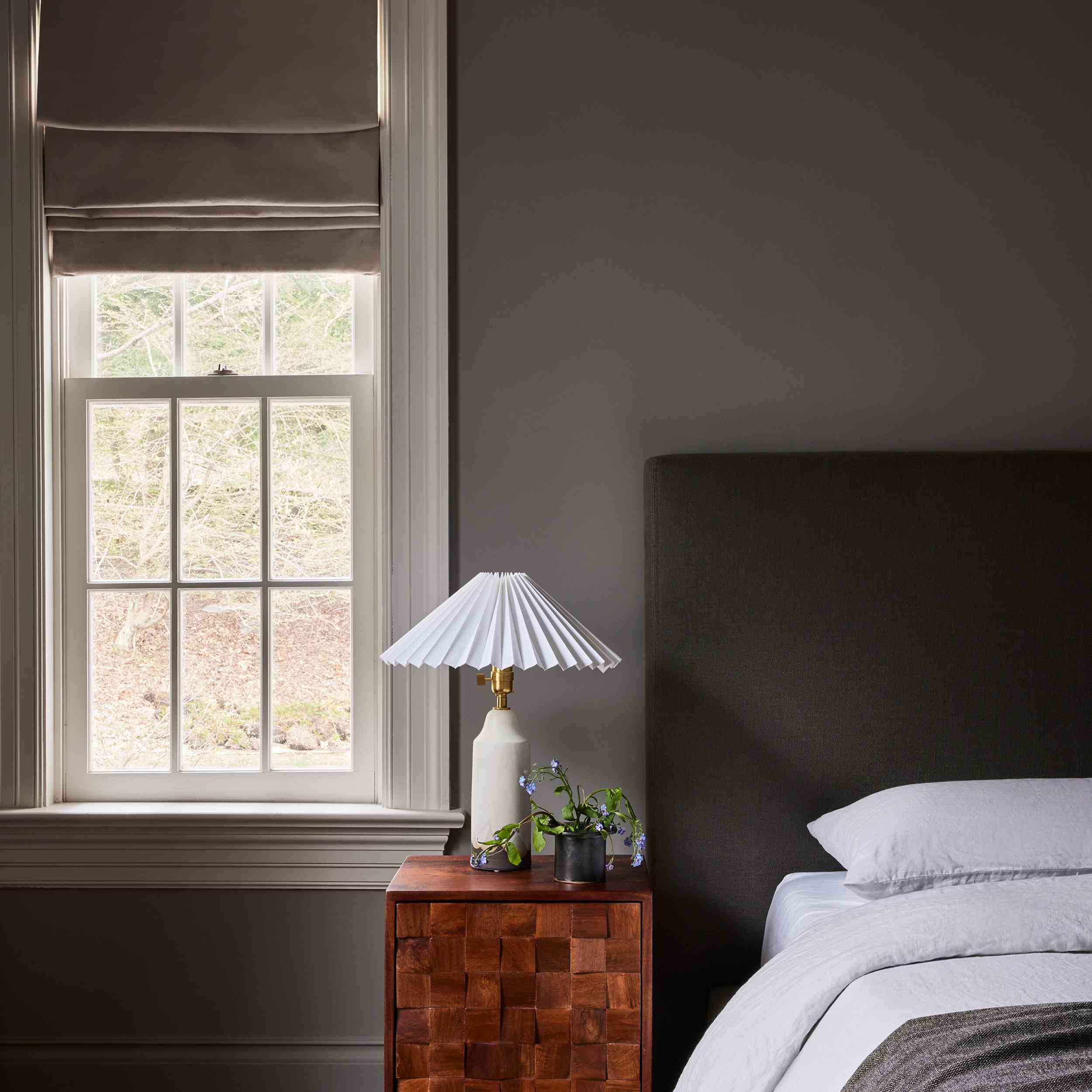connecticut farmhouse home tour - bedroom with gray walls and headboard and wooden nightstand
