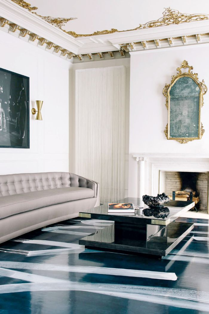 Ornate wall art complements painted floors and high ceilings of a living room