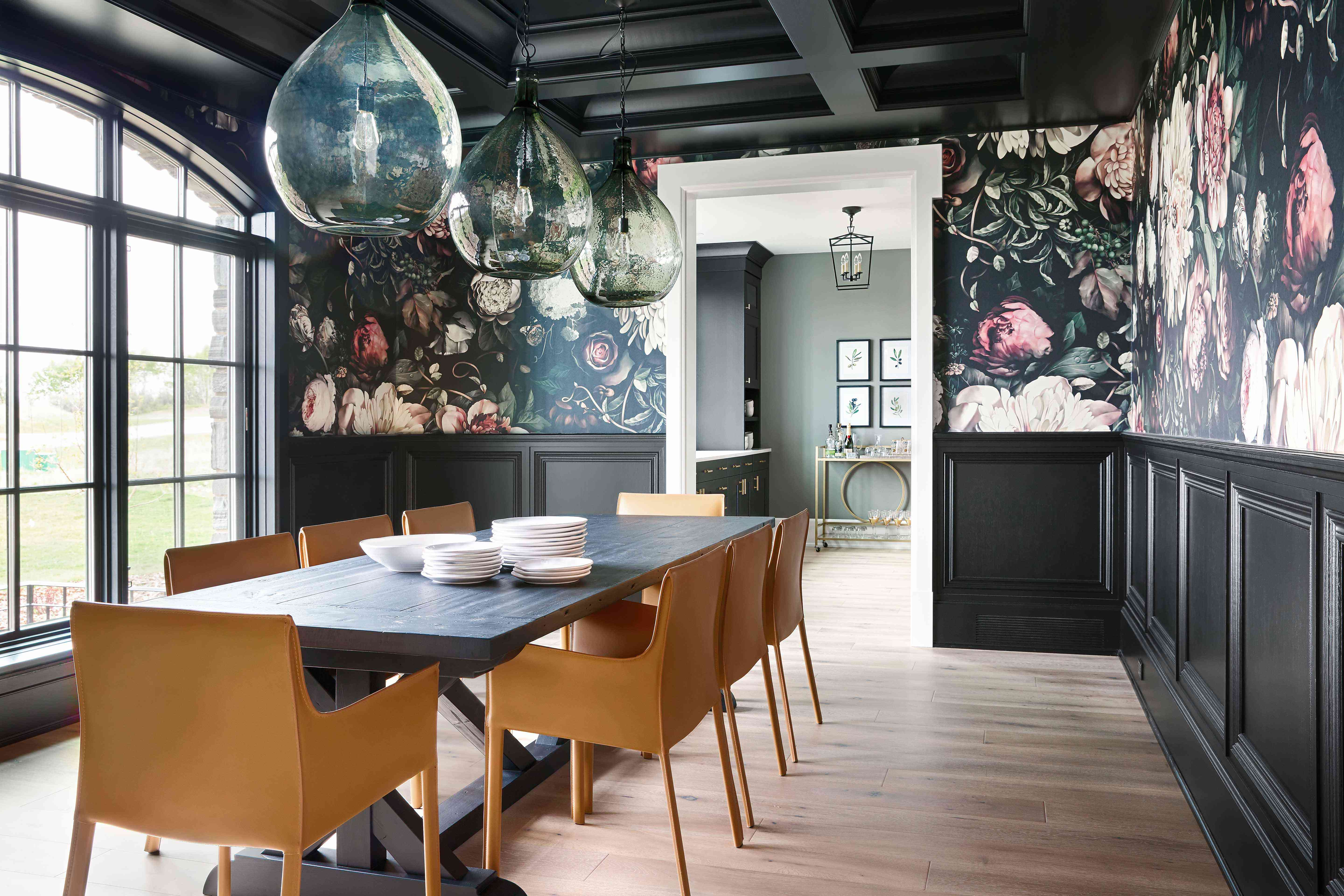 Dining room with black wainscoting and moody floral wallpaper