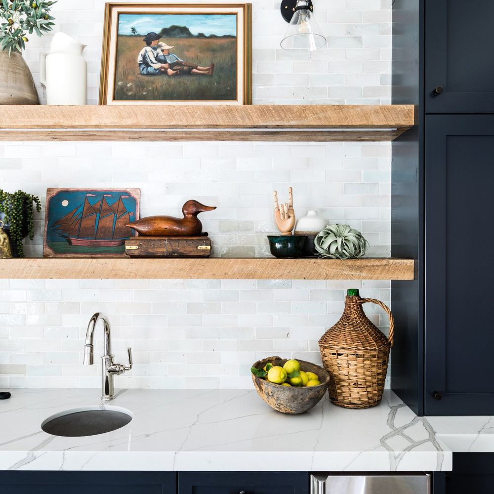 A kitchen with indigo cabinets, marble countertops, wooden shelves, and a tiled backsplash