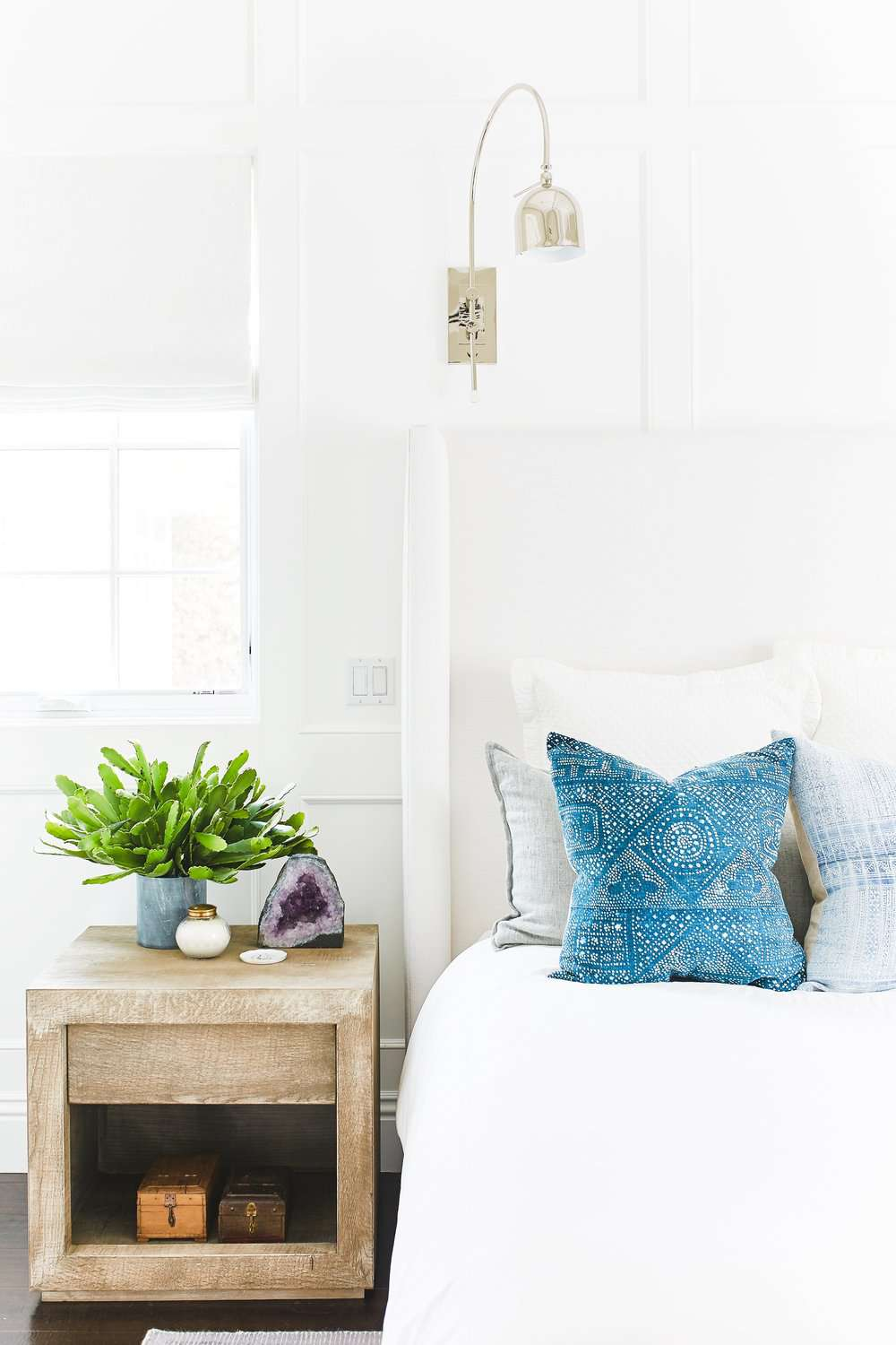 An all-white bedroom with blue pillows and a bold amethyst geode accent
