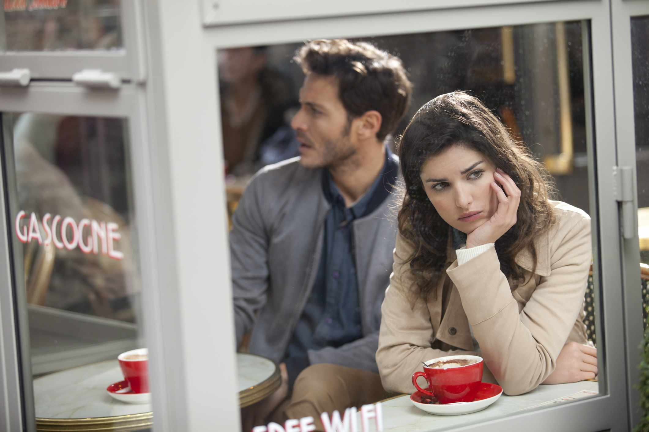 A woman looking out of a cafe window pensively, while her S.O. is in the background looking confused.