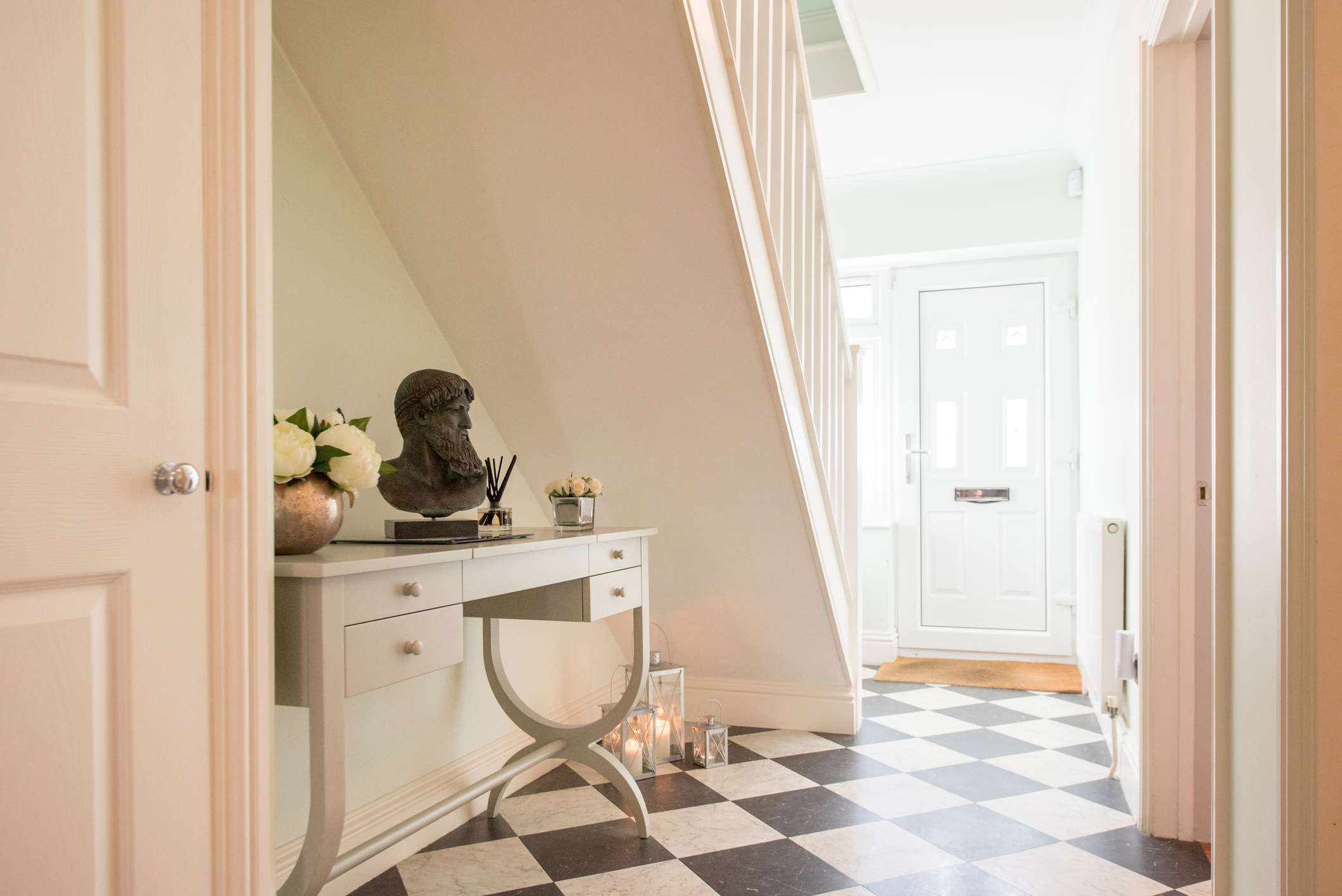A general view of a a bright hallway within a home, black and white checkered tile floors, small dresser underneath the staircase