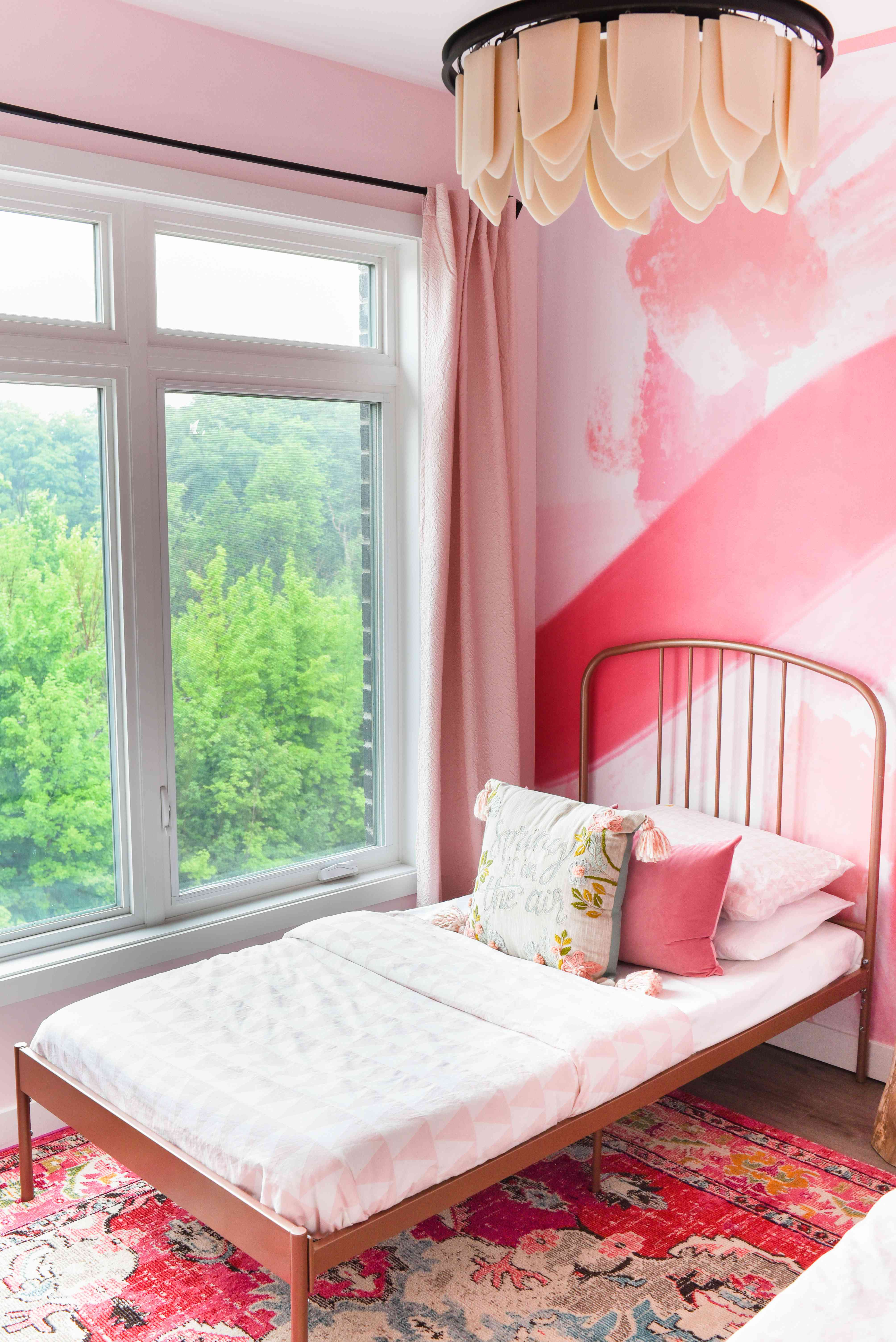 After photo of pink bedroom with metal twin bed frame.